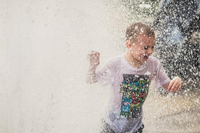 Boy Running in Fountain
