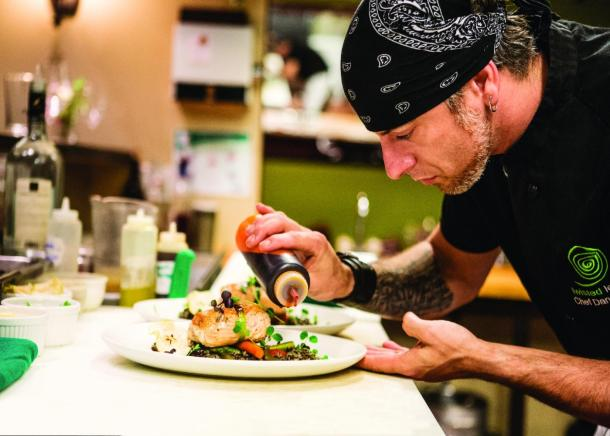 A chef from Twisted Lemon preparing a dish