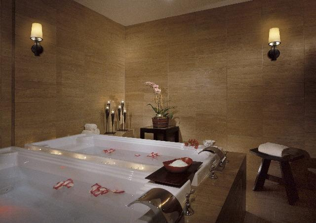 View of the Couples Hot Springs Shiatsu Tubs Inside Trellis Spa in Houston, filled with spring water and flower petals.
