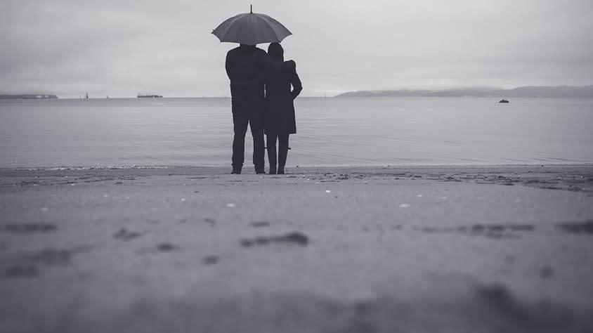 Couple on the beach in the rain