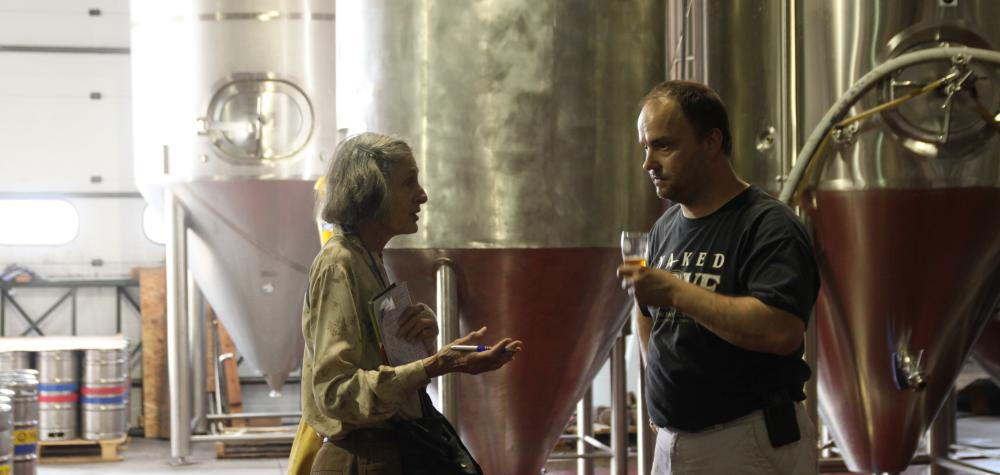 A traveler speaks with the brewmaster at Naked Dove Brewing with large, steel brewing equipment in the background.