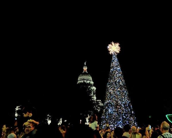 Children on adults shoulders in front of capital and christmas tree at night