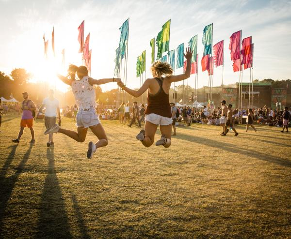 Pair of girls jumping together at sunset during ACL Festival