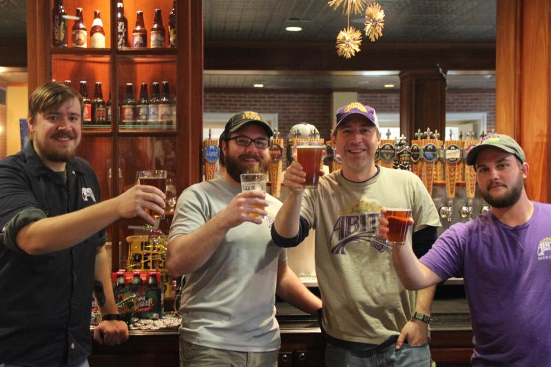 Men raising their beers at Abita Brewing Companyin Louisiana
