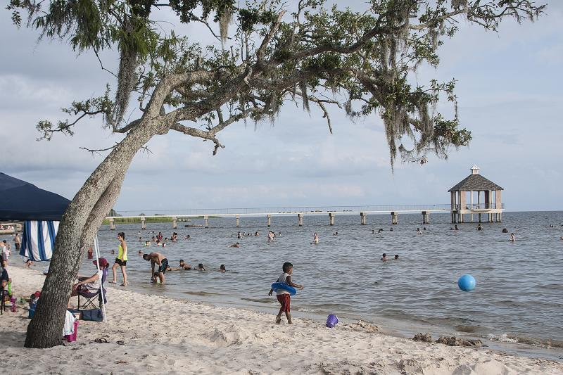 Visitors play on the beach at Fontainebleau State Park in Mandeville Louisiana