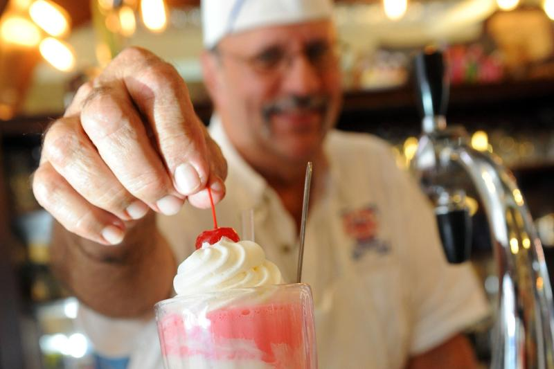 Worker placing cherry on shake at Old Town Soda Shop in Slidell