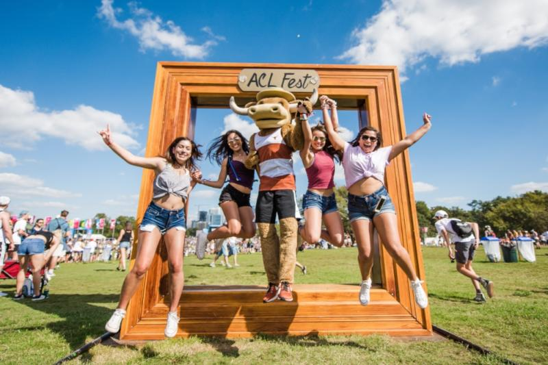 University of Texas Mascot Hook Em poses with women at the famed frame photo op at ACL Music Festival in Austin