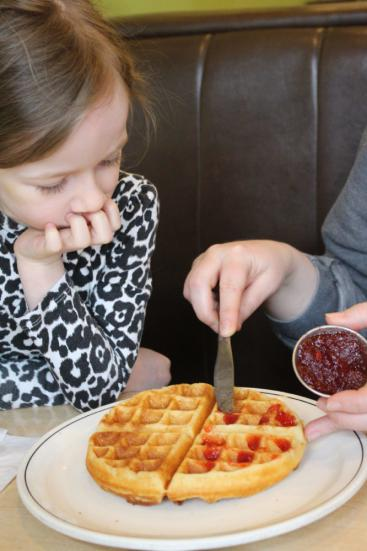 Child in a booth watching strawberry jam be spread on a waffle