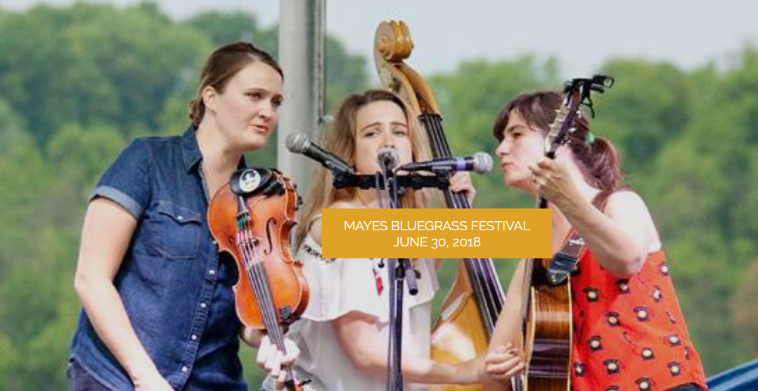 Three women gathered around a microphone singing and playing bluegrass music