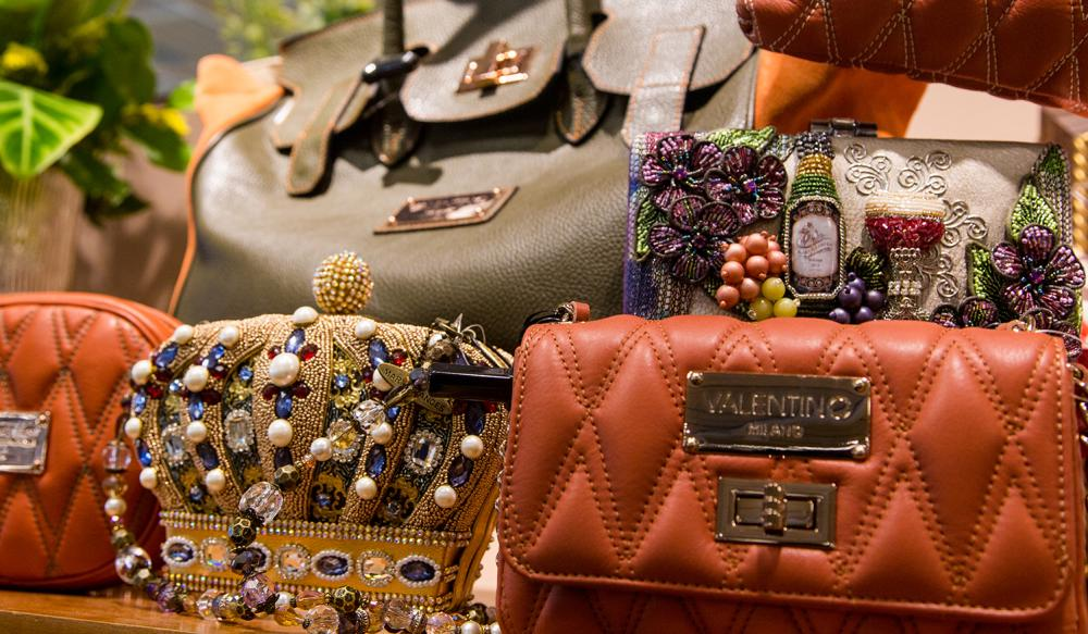 A Valentino hand bag and several other purses on a table