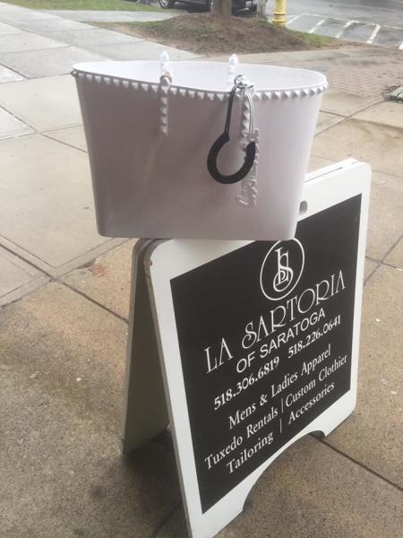 White purse on La Sartoria of Saratoga sign