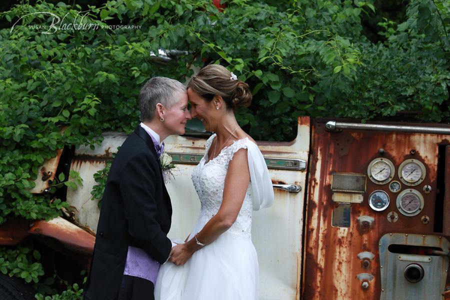 Couple holding hands and smiling after wedding in front of trees and vintage truck