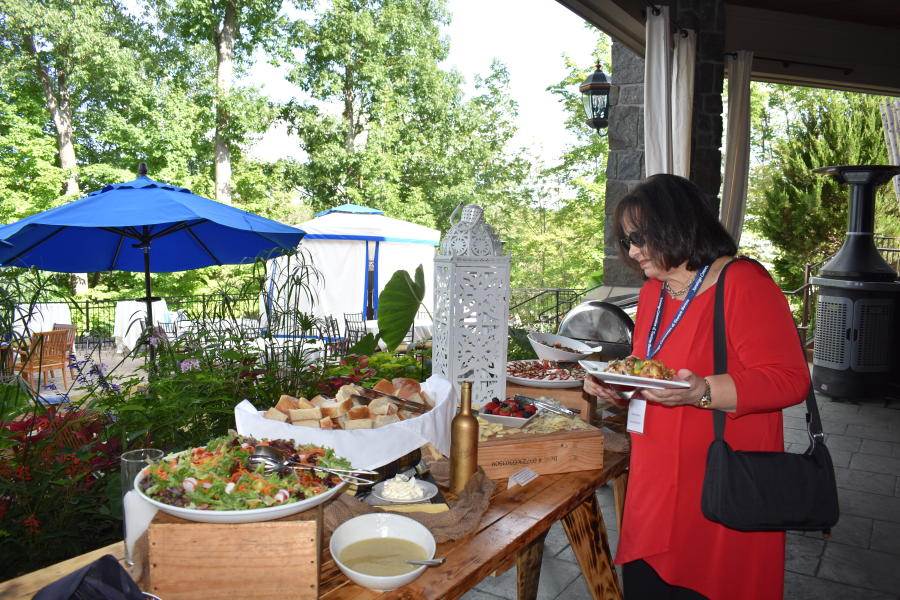 Woman at networking event at Saratoga National Golf Club grabbing food from buffet