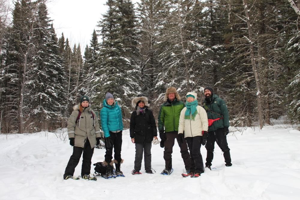six people dressed in snow suits with snowshoes in the snow with trees in the background
