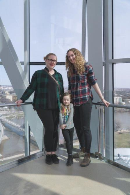 Two adults and one child pose in front of a glass wall overlooking the river and Winnipeg's St. Boniface neighbourhood.
