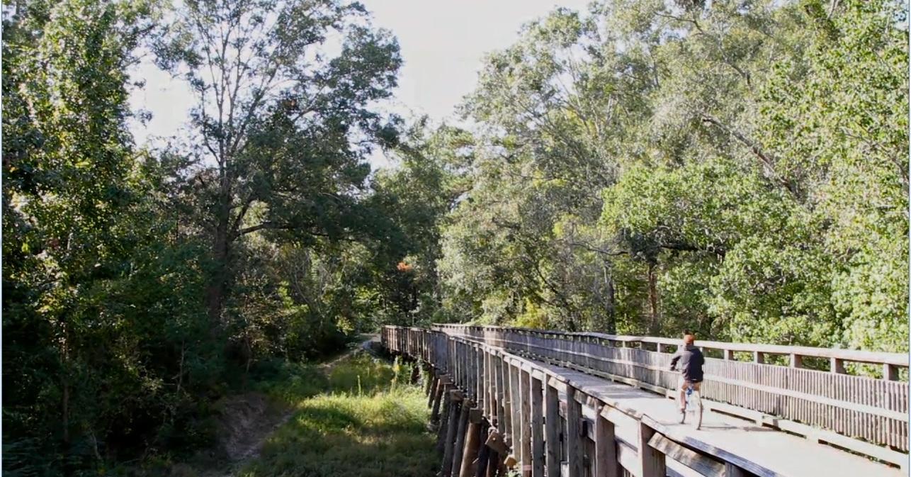 Biking across wooden bridge on the Tammany Trace