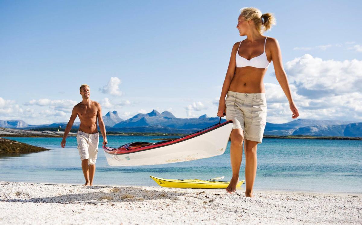 Пара на пляже с каноэ