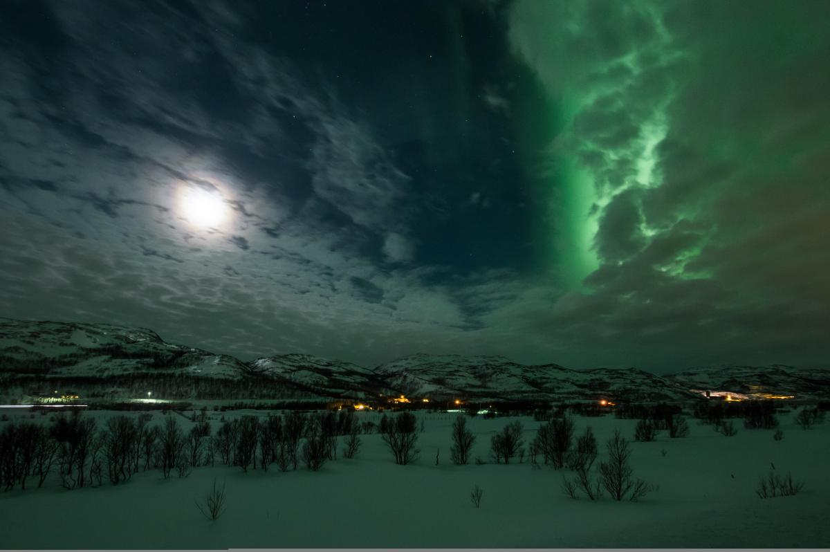 An explosion of northern lights behind the clouds resultet in the whole area glowing green