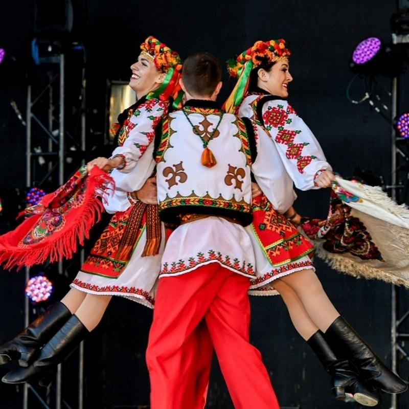 Dancer lifts two other dancers in traditional Ukrainian costumes