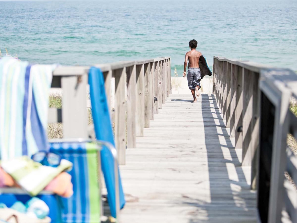 Boy running toward the ocean on a beach boardwalk