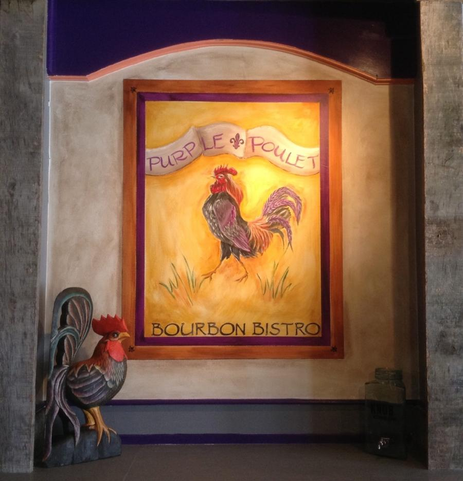 A wooden rooster in the lower corner and a painting with the words purple poulet bourbon bistro painted around a purple rooster