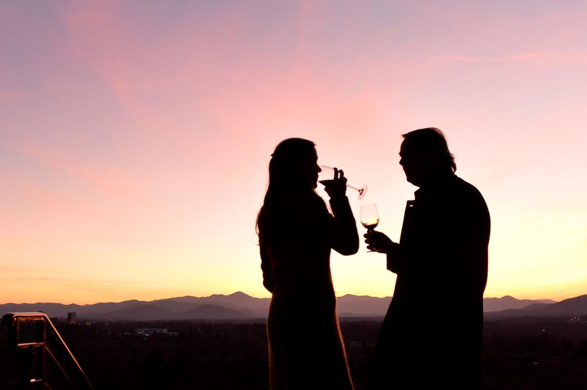 Couple drinking wine on Sunset Terrace at The Omni Grove Park Inn
