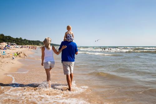 Family walking on the beach along Lake Michigan in Grand Rapids