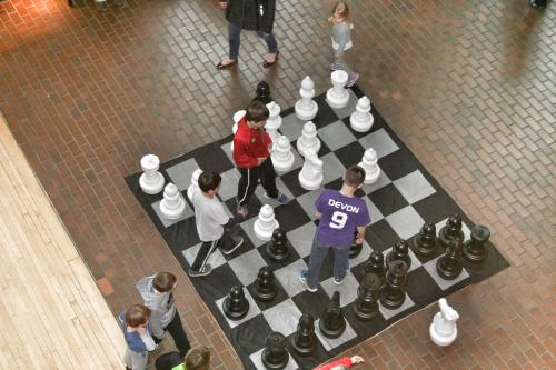 Kids playing on life size chessboard at the Grand Rapids Public Museum