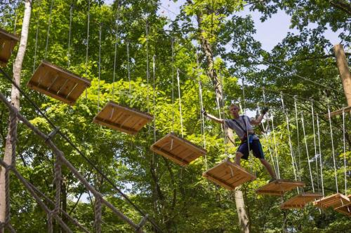 Man crossing rope bridge at Treetop Adventure Park in Grand Rapids