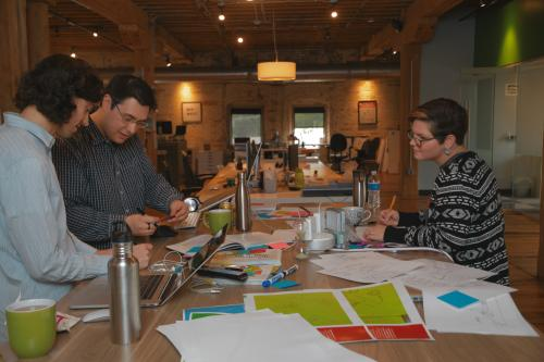 People working at shared table at Open System Technologies in Grand Rapids