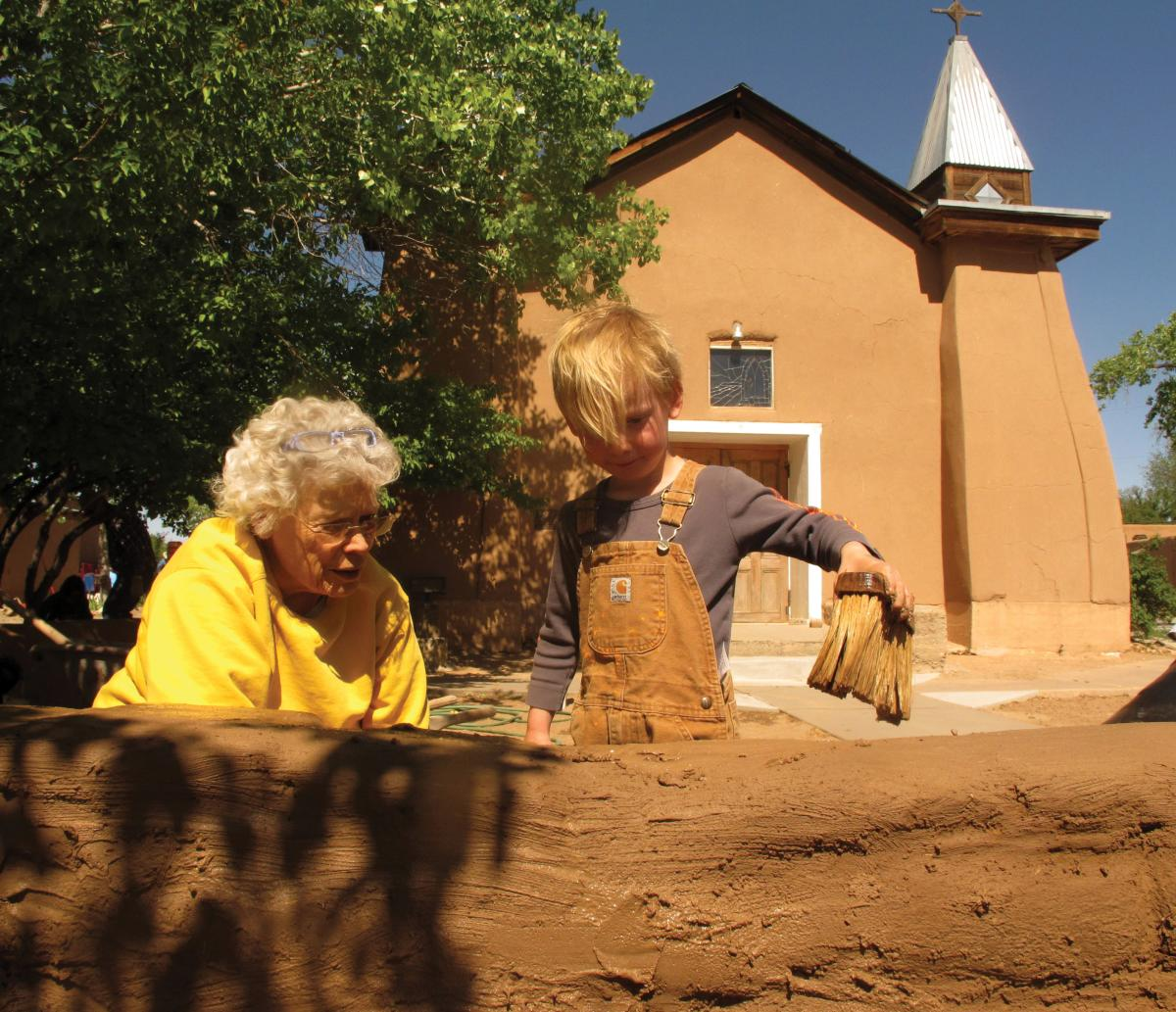 Mary Spragg and August Braude mudding a church wall