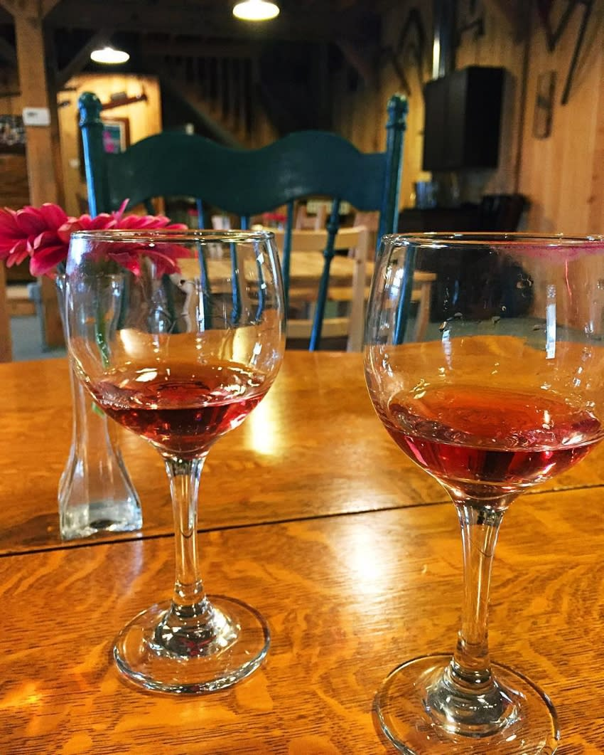 Two glasses of red wine on a wood table with red flowers