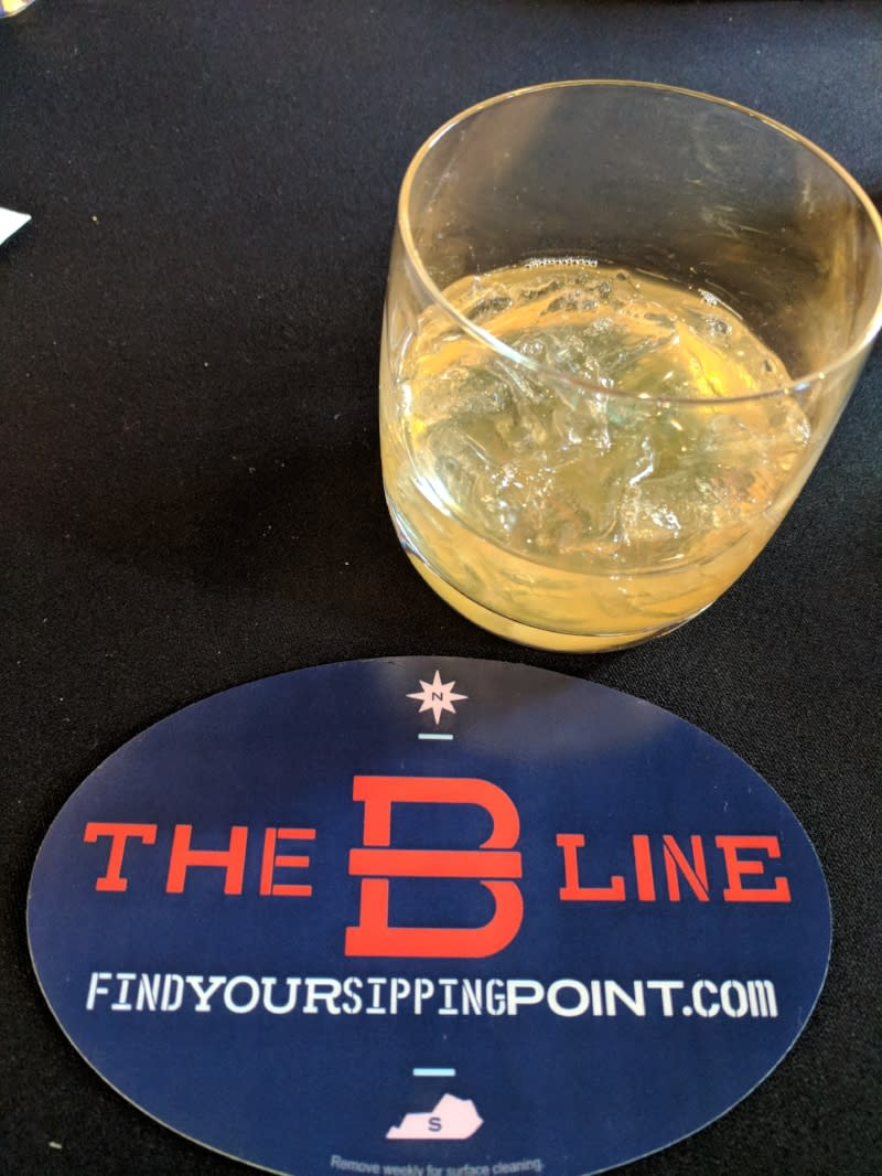 The B-Line cocktail in a bourbon glass next to a blue, red and white coaster for the B-Line