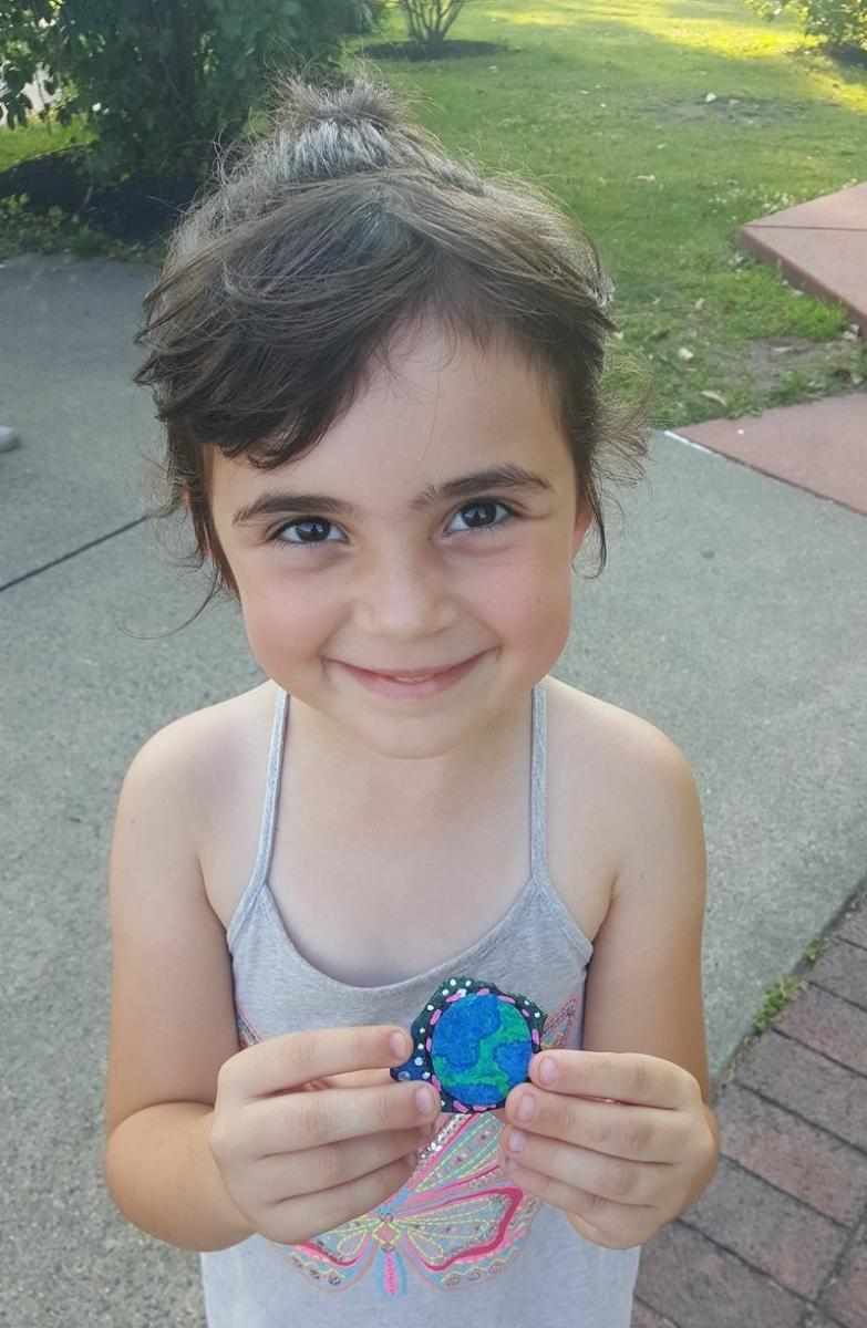 Child with blue painted rock