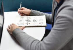 Person drawing in notebook