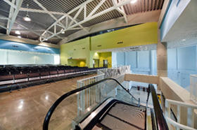 Interior photo of Cruise Terminal 21 escalator and passenger seating area