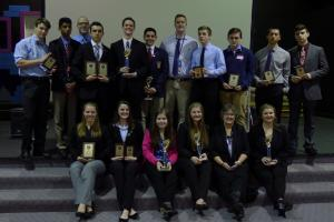 Students sit on a stair case holding awards