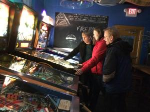 Three people playing pinball at Old Crown