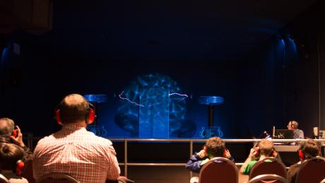a faraday cage sits on a stage surrounded by giant Telsa coils
