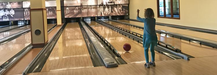 Little girl bowling at Pinstripes in Overland Park