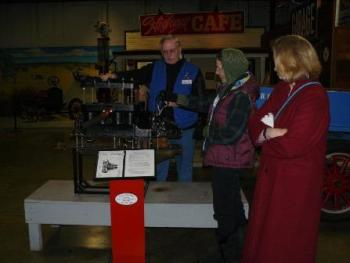 Don, the friendly California Automobile Museum docent, teaches Carol and Janet about the inner workings of an automobile.