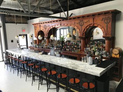 Interior view of Service Bar, featuring white marble bar, wooden stools, hanging lights, and antique wooden shelving fully stocked with bottles