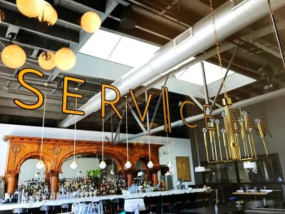 Close-up of Service Bar's store signage with interior of bar in background