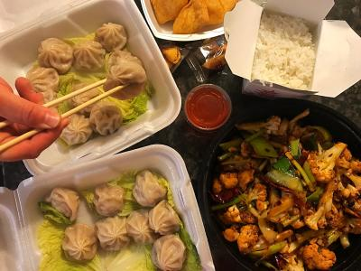 Bird's-eye view of Chinese dinner with dumplings, stir fry, and rice in take-out boxes. Hand holding chopsticks grabbing dumpling in corner.