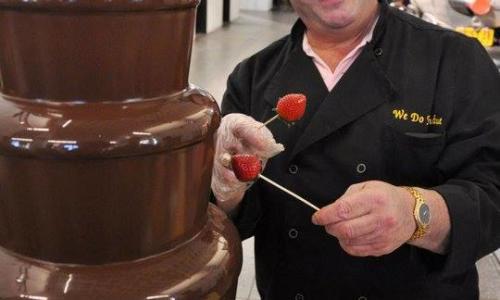 We Do Fondue Craig Wander posing with chocolate fountain and strawberries