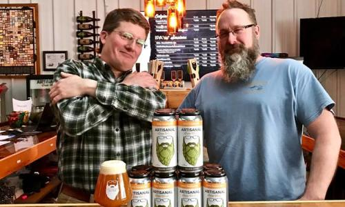 Artisinal Brew Works guys standing with pyramid of beer cans