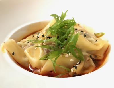 Bowl of dumplings in red sauce topped with greens and black seeds at Service Bar