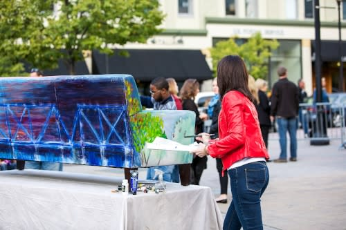 Artist painting outside during ArtPrize in Grand Rapids, MI