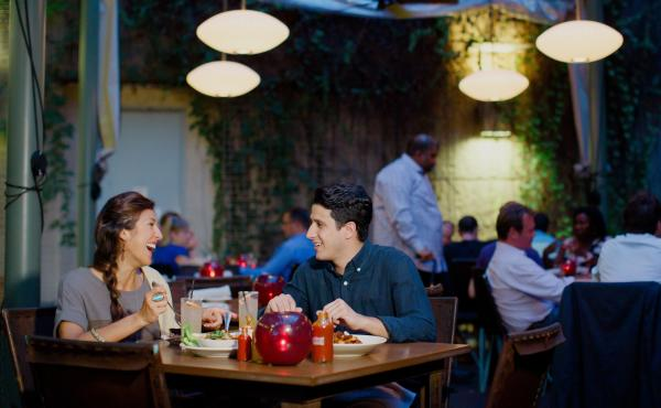Couple dining together on a patio at dusk
