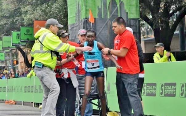 John Conley assisting a runner at the Austin Marathon.